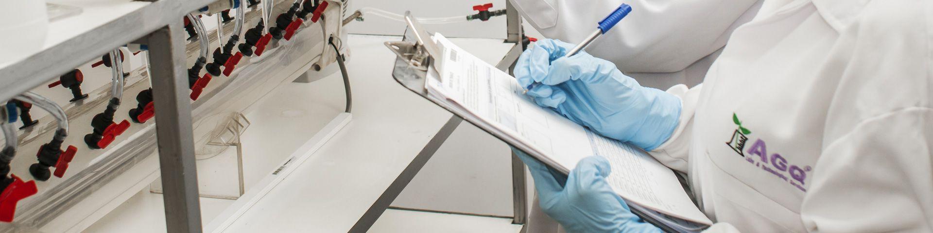 Trabajadores de AGQ Labs apuntando datos en un laboratorio